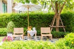 在木桌上的茶具在白色伞下在庭院里在su 免版税库存照片