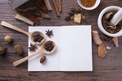 在木桌上的草药与教育的笔记本 图库摄影