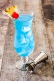在木桌上的蓝色夏威夷鸡尾酒 库存照片