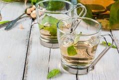 在木桌上的蓬蒿清凉茶 免版税库存照片