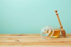 在木桌上的蜂蜜瓶子在薄荷的墙壁 犹太假日Rosh Hashana 免版税库存照片