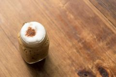在木桌上的被冰的热奶咖啡在咖啡店餐馆 免版税库存照片