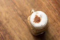 在木桌上的被冰的热奶咖啡在咖啡店餐馆 图库摄影