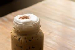 在木桌上的被冰的热奶咖啡在咖啡店餐馆 免版税库存图片