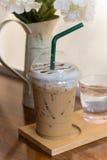 在木桌上的被冰的Capuccino咖啡与花 免版税库存照片