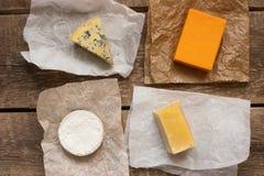 在木桌上的被分类的乳酪 免版税库存图片