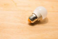 在木桌上的被带领的电灯泡 免版税库存图片