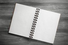 在木桌上的被检查的笔记本 图库摄影