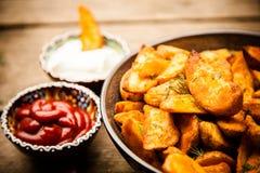 在木桌上的被烘烤的土豆油炸物 免版税库存照片