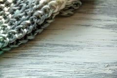 在木桌上的被编织的围巾纹理 免版税图库摄影