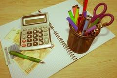 在木桌上的计算器和金钱泰国钞票 财政规划,储款的概念 免版税图库摄影