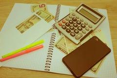 在木桌上的计算器和金钱泰国钞票 财政规划,储款的概念 免版税库存照片