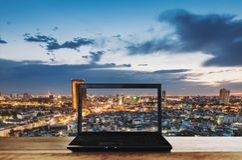 在木桌上的计算机膝上型计算机有曼谷在黄昏的市视图 裁减路线屏幕 免版税库存照片