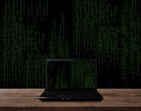 在木桌上的计算机膝上型计算机,有抽象计算机编码图表背景 免版税库存图片