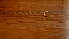 在木桌上的转动的旋转的金结婚戒指 影视素材