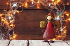 在木桌上的逗人喜爱的神仙在诗歌选金子前面点燃背景 库存照片