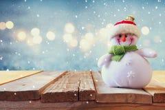 在木桌上的逗人喜爱的雪人 雪覆盖物 免版税库存照片