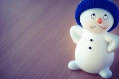 在木桌上的逗人喜爱的雪人 免版税库存图片