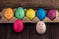 在木桌上的逗人喜爱的滑稽的复活节彩蛋 愉快的复活节 滑稽的12月 库存照片