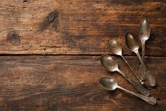 在木桌上的金属匙子 库存照片