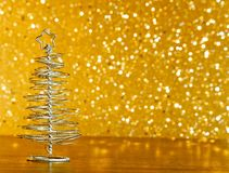 在木桌上的金属现代圣诞树在金黄色彩光bokeh背景 图库摄影