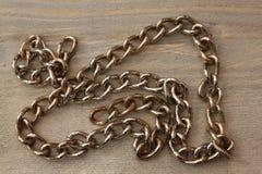 在木桌上的金属链子 免版税库存照片