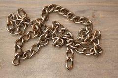 在木桌上的金属链子 库存图片