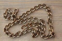 在木桌上的金属链子 库存照片