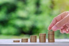 在木桌上的金币堆在早晨阳光下 事务、投资、退休,财务和节约金钱futur的 免版税图库摄影