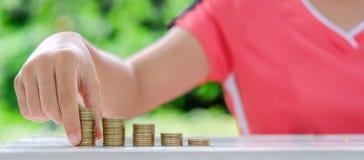 在木桌上的金币堆在早晨阳光下 事务、投资、退休,财务和节约金钱futur的 免版税库存图片