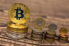 在木桌上的金黄bitcoin谎言与简单的硬币堆 图库摄影