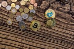 在木桌上的金黄bitcoin谎言与简单的硬币 免版税库存照片