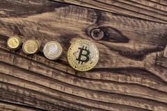 在木桌上的金黄bitcoin谎言与简单的硬币 库存照片