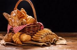 在木桌上的面包店分类在黑暗的背景 面包品种静物画与自然早晨光的 库存照片