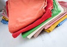 在木桌上的颜色裤子 免版税库存照片