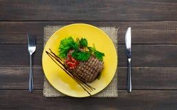 在木桌上的餐馆食物顶视图 完善的牛排 免版税库存照片