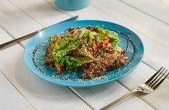 在木桌上的餐馆食物 温暖的肉沙拉用芝麻 免版税图库摄影