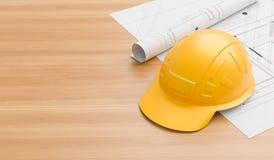 在木桌上的黄色安全帽与图纸 民工和地球移动的操作员3D例证的安全帽 库存图片