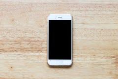 在木桌上的黑屏流动白色电话 图库摄影