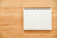 在木桌上的黏合剂笔记本 图库摄影