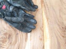 在木桌上的黑手套摩托车 免版税库存照片