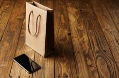 在木桌上的黑智能手机和工艺纸袋 免版税库存照片