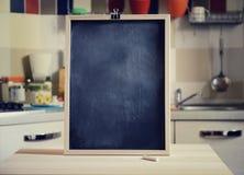 在木桌上的黑板在厨房背景 免版税库存照片