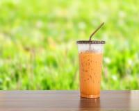 在木桌上的冻牛奶茶甜饮料 免版税库存图片