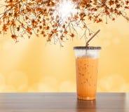 在木桌上的冻牛奶茶甜饮料 免版税图库摄影