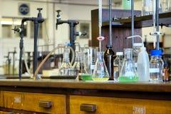 在木桌上的玻璃器皿在化工实验室 免版税图库摄影