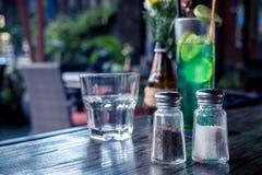 在木桌上的玻璃盐和胡椒罐在咖啡馆 巴厘岛 免版税图库摄影