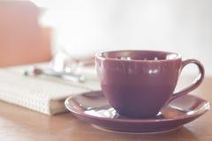 在木桌上的紫罗兰色咖啡杯 库存照片