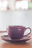 在木桌上的紫罗兰色杯子 免版税库存照片