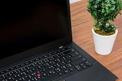 在木桌上的黑膝上型计算机 免版税图库摄影